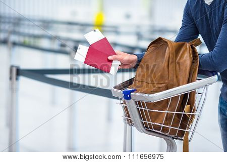 Young man with passports and boarding passes at the front desk at airport waiting for flight