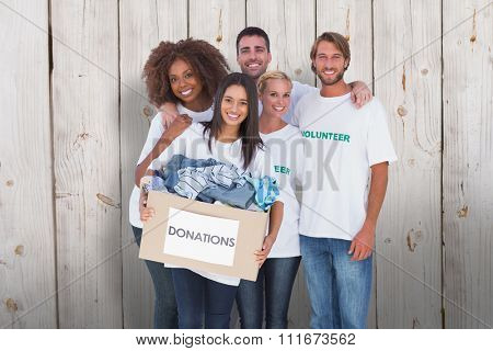 Happy group of volunteers holding donation box against wooden background