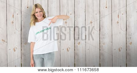 Portrait of a happy female volunteer pointing to herself against wooden background