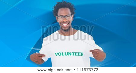 Handsome man pointing to his volunteer tshirt against abstract blue design