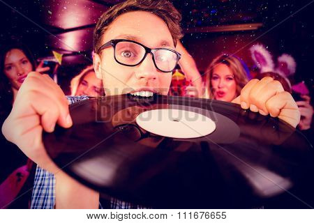 Geeky hipster biting vinyl record against pretty friends on a hen night