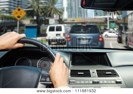 Car driver hands. People driving on driveway.