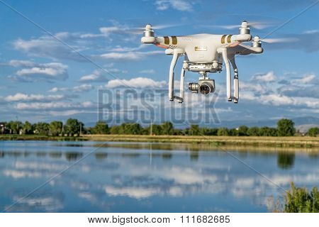 FORT COLLINS, CO, USA, SEPTEMBER 7 , 2015:  DJI  Phantom 3 quadcopter drone flying with a camera over a lake.