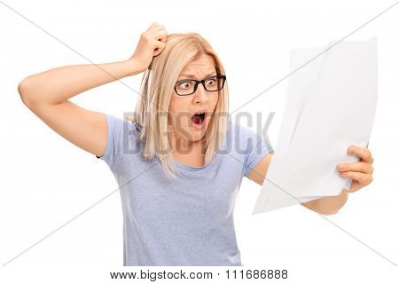 Shocked blond woman looking at a piece of paper in disbelief isolated on white background