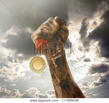 Golden medal in dirty hand on sky background