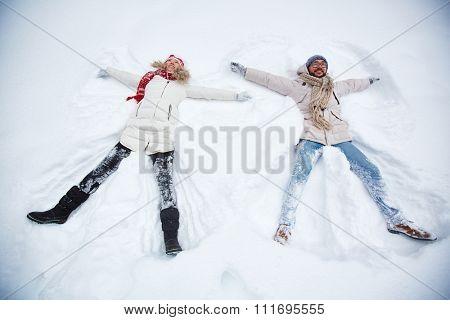 Happy couple in winter-wear lying in snowdrift