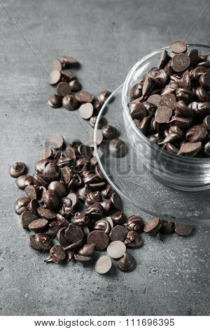 Chocolate morsels in glass mug on gray background