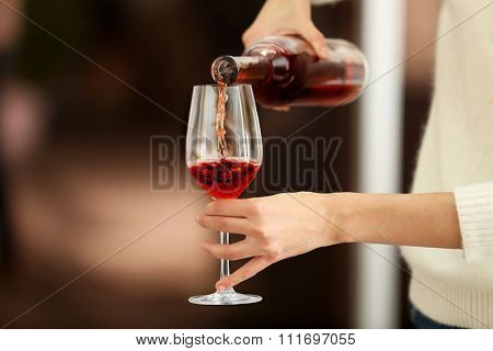 Young woman pouring pink wine into glass on blurred background