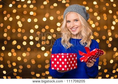 Portrait of a happy woman opening gift box over holdays lights background
