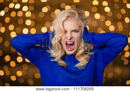 Portrait of a blonde woman covering her ears and screaming over holidays lights background