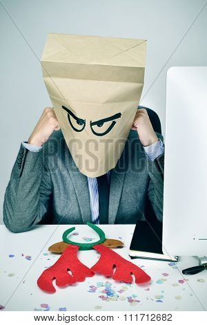 a young caucasian businessman with a paper bag in his head with a sad face sitting at his office desk, with a reindeer antler headband and covered with confetti