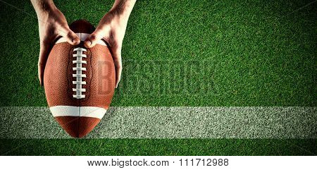 American football player holding up football against pitch with line