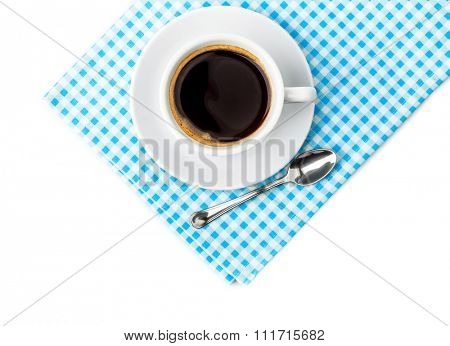 White coffee cup with saucer and spoon tableware on blue chequered napkin. Isolated on white background