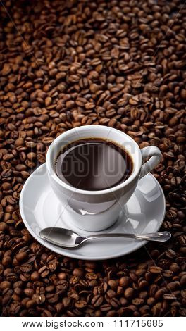 Hot fragrant coffee drink in white porcelain cup with saucer and spoon on beans background