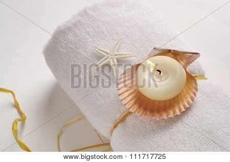 Aromatic candle with natural shells placed on white rolled towel - spa still life