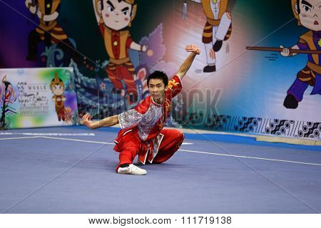 JAKARTA, INDONESIA - NOVEMBER 17, 2015: Dominic Chow of the USA performs the movements in the men's Compulsory Changquan event in the 13th World Wushu Championship 2015 in Istora Senayan Stadium.