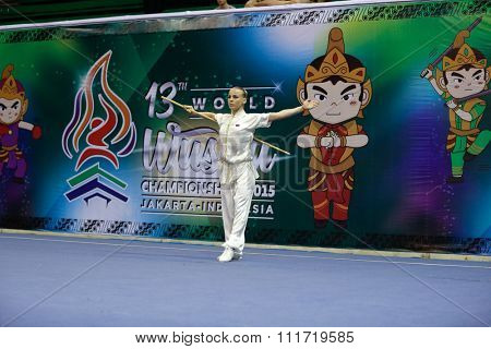 JAKARTA, INDONESIA - NOVEMBER 17, 2015: Daria Tarasova of Russia performs the movements in the women's Gunshu event at the 13th World Wushu Championship 2015 in Istora Senayan Stadium.