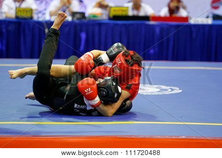 JAKARTA, INDONESIA - NOVEMBER 17, 2015: Cristiana Stancu of Romania (red) fights Maryam Hashemiforoud of Iran (black) in the men's 70kg Sanda event at the 13th World Wushu Championship 2015.