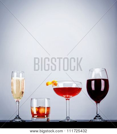 a line of cocktails on a bar studio shot on a gray background with side lights and reflections and space for text