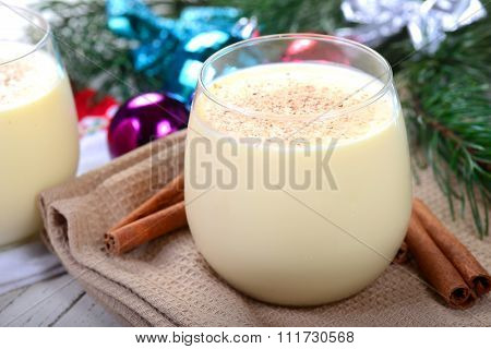 Glass of delicious eggnog displayed in a festive Christmas setting with a shallow depth of field
