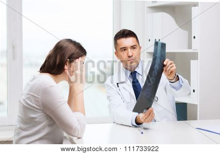 healthcare, surgery, rontgen, people and medicine concept - smiling male doctor in white coat with laptop computer looking at x-ray in medical office