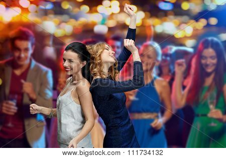 party, holidays, nightlife and people concept - happy young women dancing at night club disco over night lights background