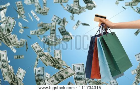 people, sale, finance and consumerism concept - close up of male hand holding shopping bags and bank or credit card over blue background and money rain