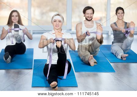 Fitness stretching practice group of four beautiful happy fit young people working out in sports club doing hamstring stretch exercises with props belts on blue mats in class poster