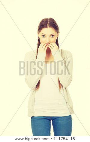 Nervous pensive teenage woman biting nails.