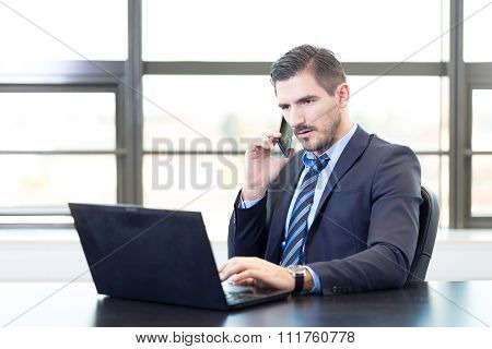Businessman in office working on laptop computer.