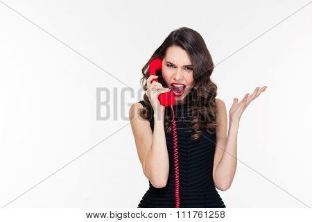 Hysterical aggressive young female with bright makeup in retro style shouting and talking on red telephone over white background