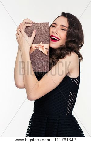 Excited elated pretty young woman with retro hairstyle in black dress hugging gift box over white background