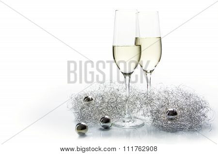 Two Flutes Champagne Glasses For New Year And Silver Decoration On White