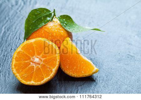 Fresh dewy mandarin placed on black stone.