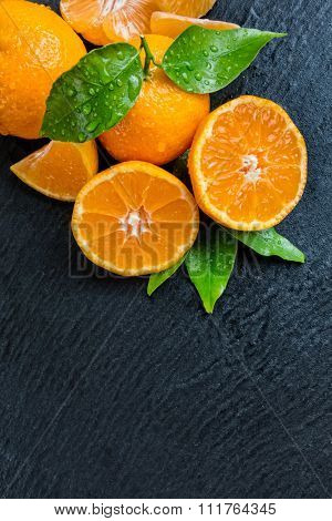 Fresh dewy mandarin placed on black stone, top view. Copyspace for text poster