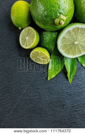 Fresh dewy limes place on black stone, top view. Copyspace for text