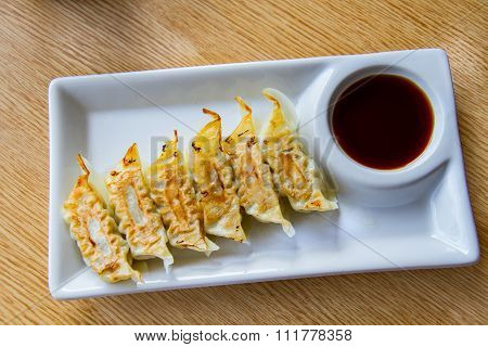 Asian appetizer menu fried dumplings with soy sauce Japanese tone