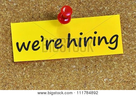 We're Hiring Word On Yellow Notepaper With Cork Background
