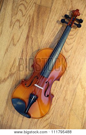A 3/4 size Violin lays on a hard wood background with beautiful light and shadows for a unique view. Violins are part of the music world, some are worth millions of dollars.