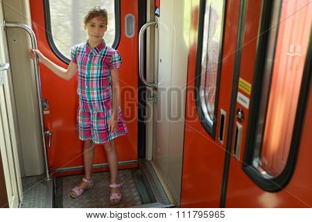 Young girl standing in vestibule of train and hold handrail
