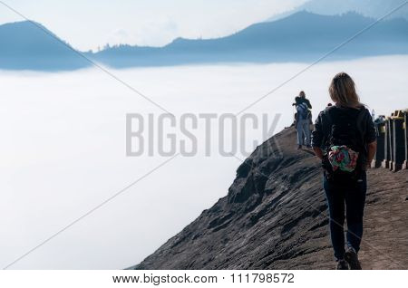 Woman walking along top of volcano next to fog and mist