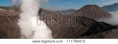 Volcano Bromo Errupting Smoke and sulphur under blue sky