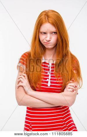 Pretty cute sad offended girl with beautiful red hair standing with hands crossed over white background