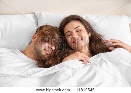 Happy couple snoozing on bed