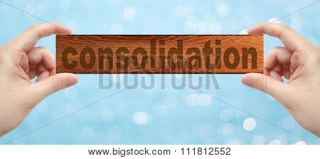 Hands Holding A Wood Engrave With Word Consolidation