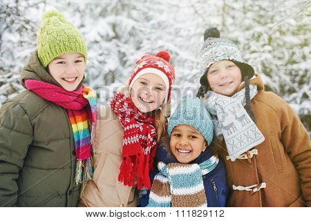 Friendly kids in winterwear looking at camera in natural environment in winter