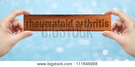 Hands Holding A Wood Engrave With Word Rheumatoid Arthritis