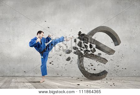 Young determined karate man breaking with leg concrete euro sign