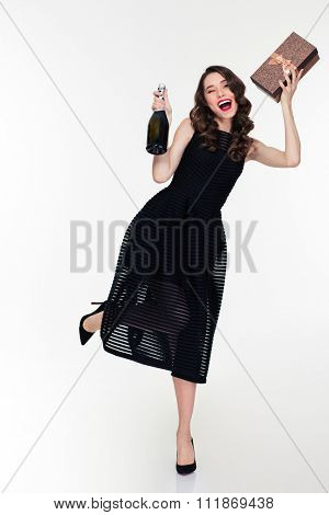 Positive joyful lovely young woman with retro hairstyle in clasical black dress dancing holding gift box and bottle of champagne
