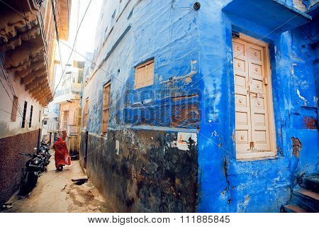 Narrow Indian Street With Blue Houses And Rushing Indian Woman In India